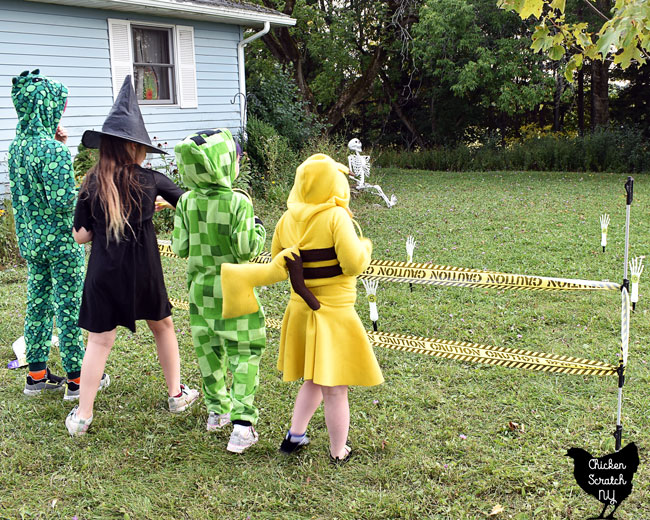 four kids in costumes playinf Skelton Ring toss Halloween party game with skeleton hand lawn stakes and glow ring necklaces