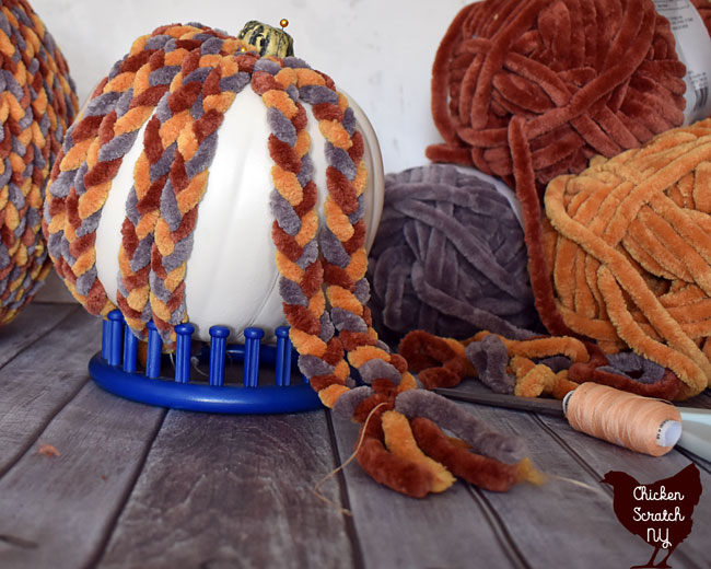 fake pumpkin held up with a blue stand being covered with braids made from chunky chenille home yarn being tied together to stop from unraveling