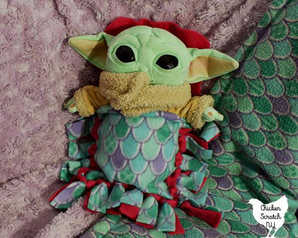 baby yoda stuffed animal in a fleece sleeping bag