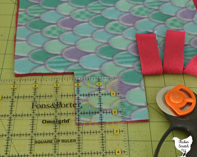 use the rotary cutter, mat and ruler to cut 1 inch wide slits all around the blanket