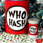 "standard sized tin can with black, red and white ""Who Hash"" label next to a wooden spool with matching label on a red, green and white paper with sparkly tinsel background with text over lay ""How the Grinch Stole Christmas Who Hash Decorations"""