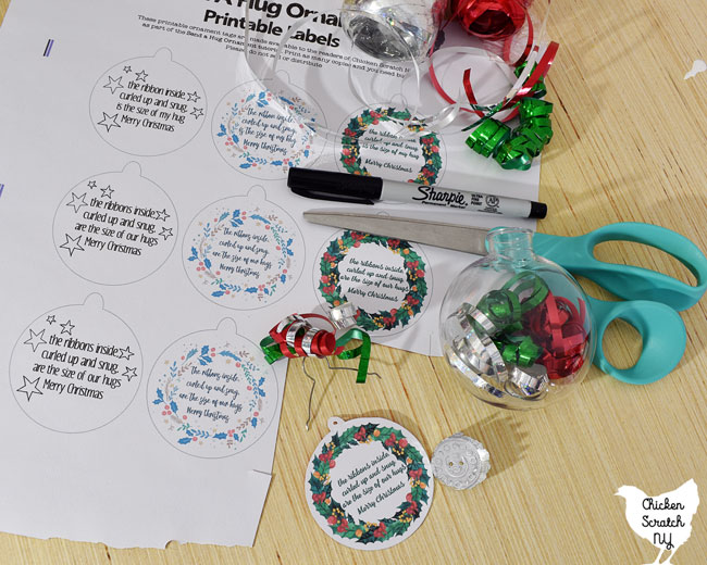 supplies to make a DIY send a hug ornament including a clear plastic ornament, three colors of curling ribbon, scissors, a sharpie and printed Christmas tags with a ribbon poem
