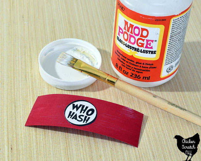 "use mod podge to apply printed and cut out ""who hash"" label to red paper"