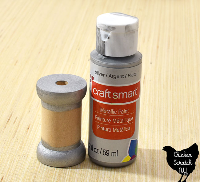 paint the top and bottom sections of a wooden spool with metallic silver paint