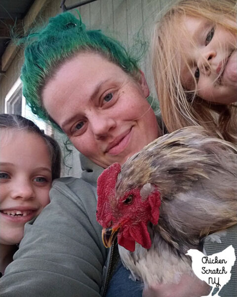 adult woman with green hair holding a large grey cochin rooster sitting with two children