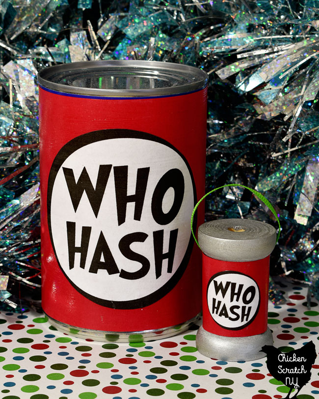 "standard sized tin can with black, red and white ""Who Hash"" label next to a wooden spool with matching label and green ribbon hanging loop on a red, green and white paper with sparkly tinsel background"