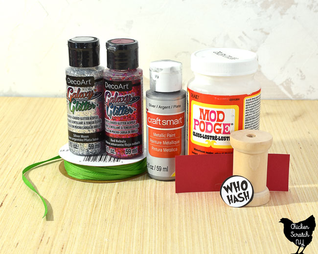 supplies for a Dr Seuss inspired christmas ornaments including red and white galaxy glitter paint, silver paint, ribbon, mod podge, wooden spool and paper label