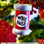 "wooden spool ornament hanging in a Christmas tree with a homemade label saying ""Who Hash"""