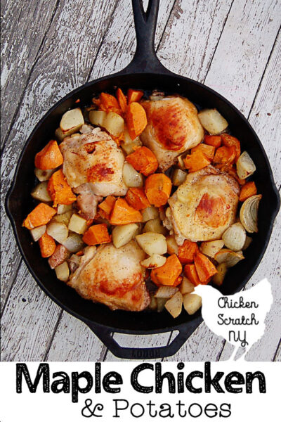 top view of lodge cast iron skillet filled with roasted onions, sweet potatoes, white potatoes and chicken thighs