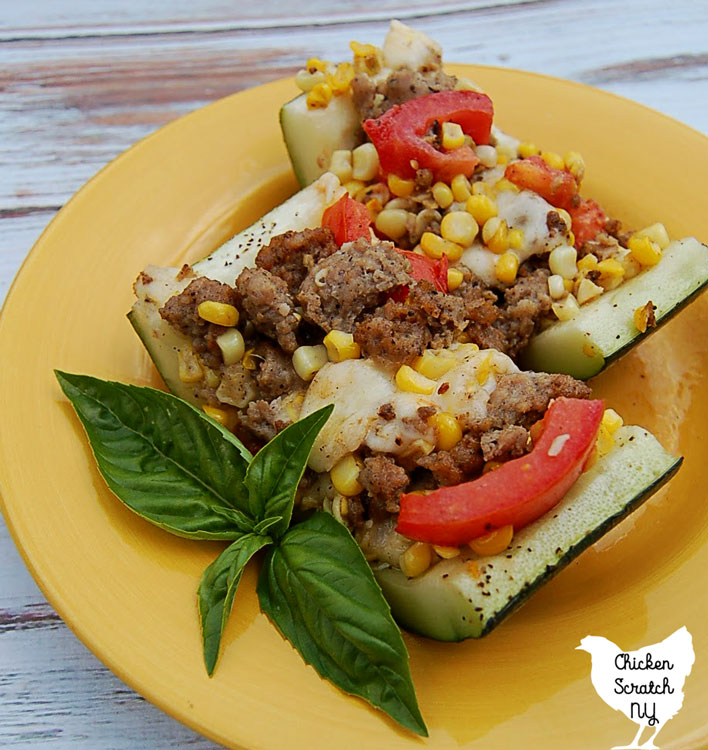 view of stuffed zucchini filled with fresh sweet corn, chopped tomatoes, mozzarella and sausage