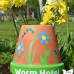 """upturned flower pot with hand painted flowers and text """" worm hotel"""" painted on the brim sitting in garden soil with yellow and white daffodils in the background with text overlay"""" Easy & Fun DIY Garden Art"""""""