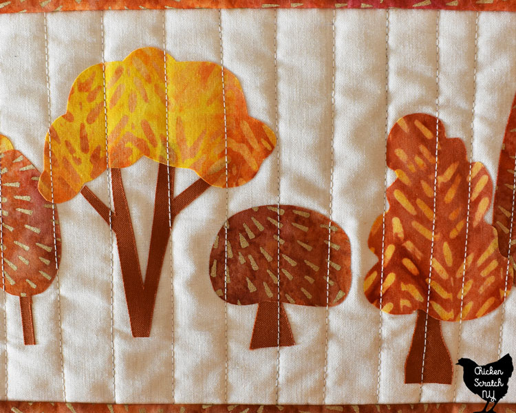 close of of finished fusible appliw autumn tree table runner with straight line stitching
