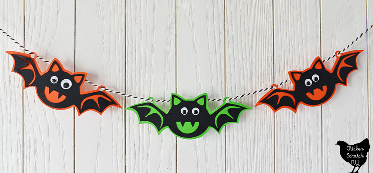 Paper Halloween bat banner hanging on a white wall, bats are made from orange, green and black card stock cut with a silhouette cameo and googley eyes