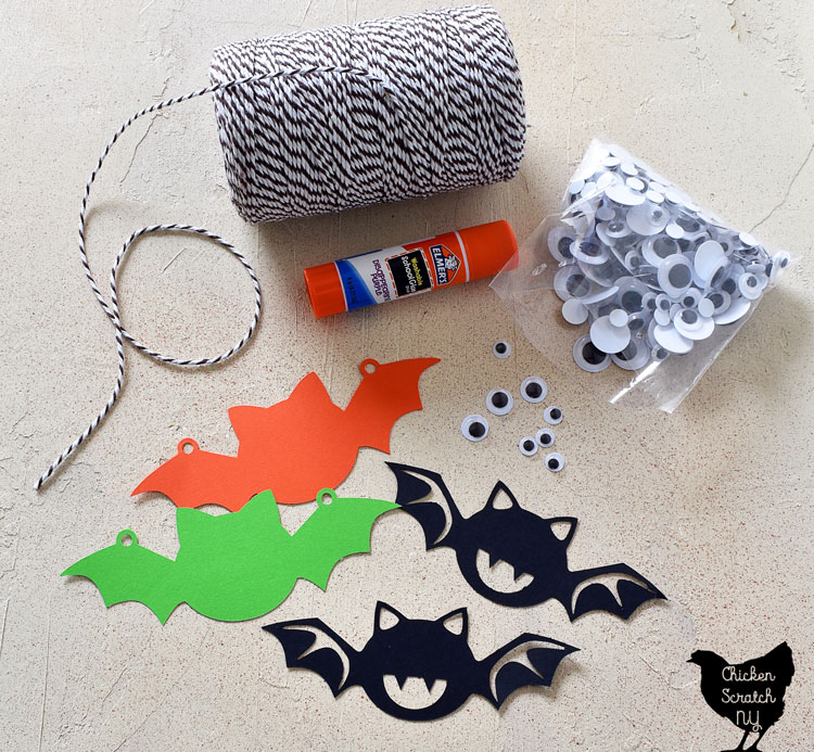 supplies for Halloween bat garland made with card stock paper, googly eyes, a glue stick and bakers twine