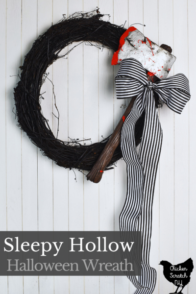 sleepy hollow inspired Halloween wreath with a bloody axe and a black and white striped ribbon