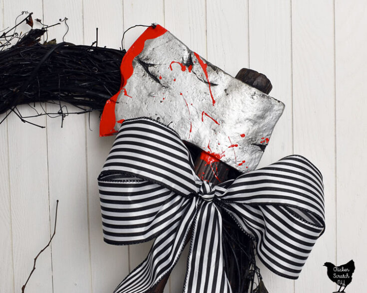 sleepy hollow inspired wreath with black and white striped bow and fake axe with blood splatter on it