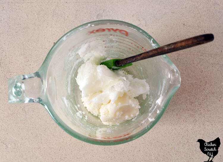solid mango and shea butter in a glass measuring cup with a spatula