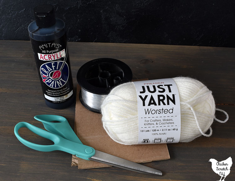 yarn ghost supplies including white dollar tree yarn, fishing line, black craft paint, scissors and cardboard template
