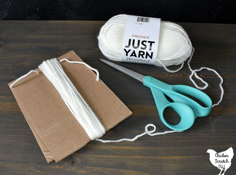 cardboard template for making a yarn tassel ghost with white yarn and a pair of scissors