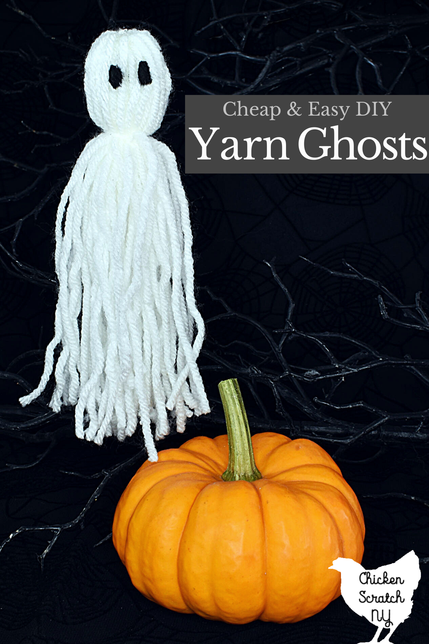 single white yarn ghost hanging from fishing line with a small orange pumpkin