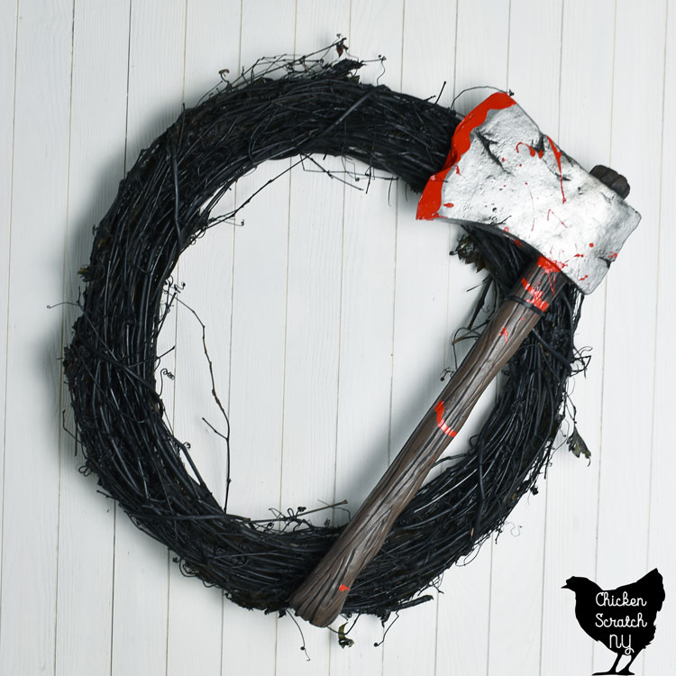 black grapevine wreath with bloody axe on it